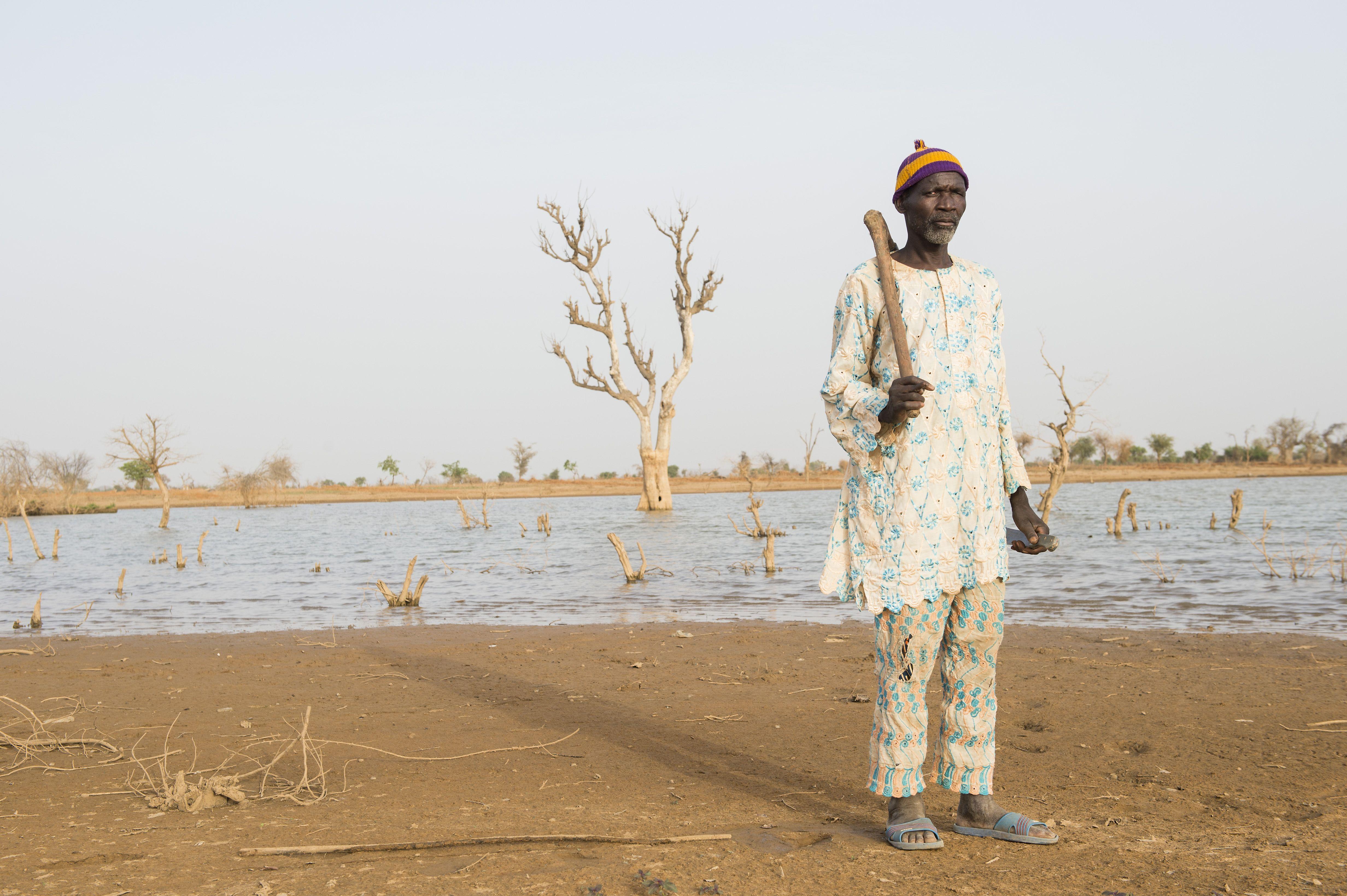 Un paysan devant son champ  inondé à cause de la mine. ©Meinrad Schade/Action de Carême