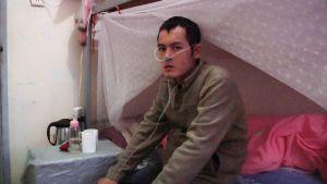 """Ming Kunpeng (26 ans) souffre d'une leucémie aiguë après avoir été en contact régulier avec le benzène. « Cela devrait être les meilleures années de sa vie » soupire son père Gaosheng. Image tirée du documentaire """"Who Pays the Price? The Human Costs of Electronics"""" d'Heather White"""